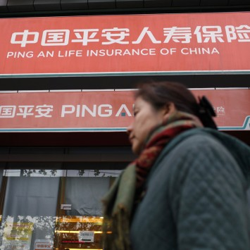 A woman walks past a Ping An Insurance building in Shanghai