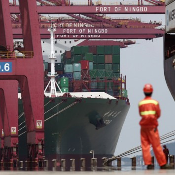 An employee stands next to a container ship at Ningbo port in Ningbo