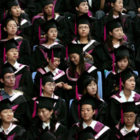 Two graduates play during a graduation ceremony in Beijing