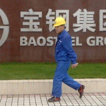 A labourer walks past the gate of the headquarters of Baosteel Group Corp. in Shanghai