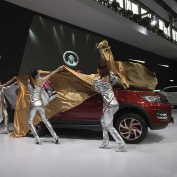 Staff uncover a Great Wall Motors Haval M4 mini SUV during the media preview of the 10th China International Automobile Exhibition in Guangzhou
