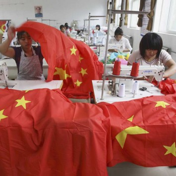 Workers sew Chinese national flags at a factory on the outskirts of Beijing