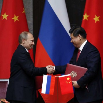 Russia's President Vladimir Putin and China's President Xi Jinping shake hands after signing an agreement during a bilateral meeting in Shanghai