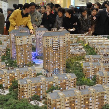 Visitors look at model apartments at a real estate exhibition in Shenyang