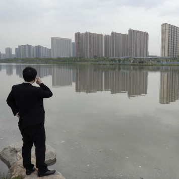 A man talks on his phone near a new residential compound in Taiyuan