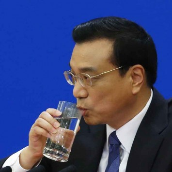 China's Premier Li Keqiang drinks during a news conference in Beijing