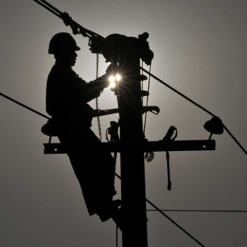 A worker repairs an utility pole on the outskirts of Yingtan, Jiangxi province