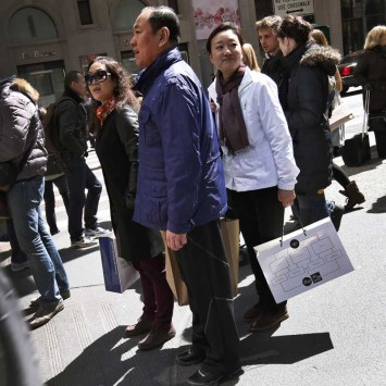 Chinese shoppers stand with shopping bags on a sidewalk along 5th Avenue in New York