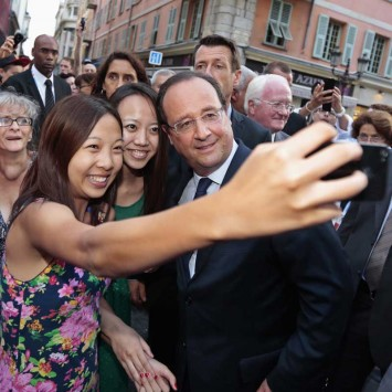 Tourists take a photo of themselves with France's President Francois Hollande ahead of the opening ceremony of the 7th Francophone Games in Nice