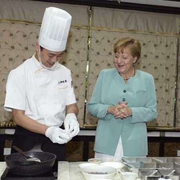 German Chancellor Merkel looks on as a Chinese chef demonstrates how to make kung pao chicken, at a restaurant in Chengdu