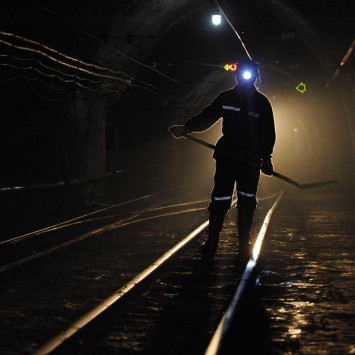 A miner walks along tracks used for transporting coal in an underground coal mine in Xiaoyi, Shanxi province