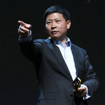 Huawei CEO Yu points to a journalist as he stands near the presenter of the event, after the Huawei presentation before the start of the Mobile World Congress in Barcelona