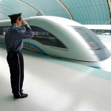 Chinese security personnel salutes from platform next to maglev train in Shanghai
