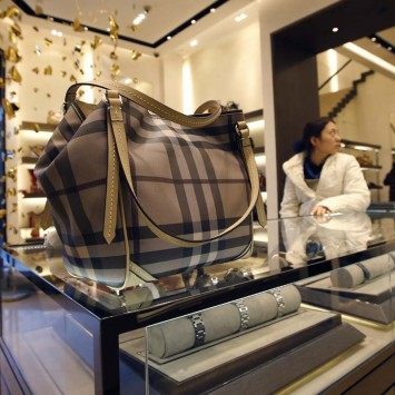 A Burberry handbag is seen on glass display cases at a Burberry store in Beijing