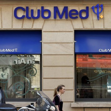 A woman walks past a Club Med travel agency in Paris