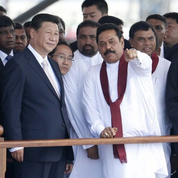 China's President Xi Jinping looks as Sri Lanka's President Mahinda Rajapaksa points to the sea during the launch ceremony of a $1.5 billion project to build a port city on reclaimed land in Colombo