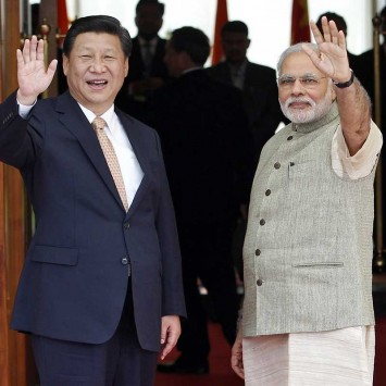 India's PM Modi and China's President Xi wave before their meeting in Ahmedabad