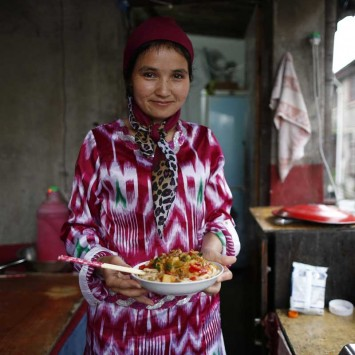 Youssef, an Uighur woman, holds a dish of Xinjiang noodles as she poses for a photograph at her home in Shanghai