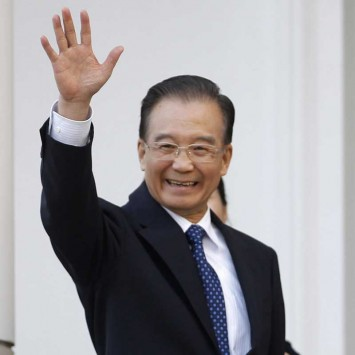 China's Premier Wen Jiabao waves to the members of the press at the Belweder Palace in Warsaw