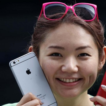 A woman holds a mock iPhone 6 plus and an iPhone 5s as she waits in a line, ahead of the September 19 release of iPhone 6 and iPhone 6 Plus, in front of an Apple Store at Tokyo's Ginza shopping district