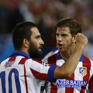 Atletico Madrid's Arda is congratulated by teammate Ansaldi after scoring against Juventus during their Champions League Group A soccer match at Vicente Calderon stadium in Madrid
