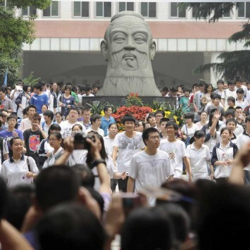 Parents take photos of students walking past a statue of Confucius, after the first test of the National College Entrance Exams in Wuhan