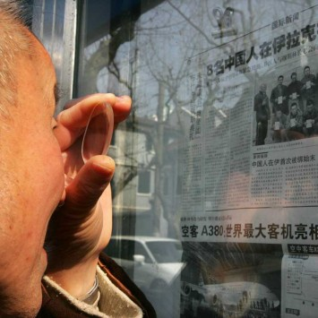 Chinese man uses a magnifying glass to read a newspaper in Shanghai.