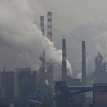 Smoke rises from chimneys and facilities of steel plants on a hazy day in Benxi