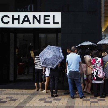 Mainland Chinese tourists wait outside a Chanel store at Hong Kong's Tsim Sha Tsui shopping district