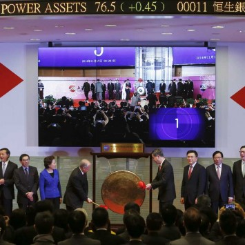 Hong Kong Exchanges and Clearing Ltd. Chairman Chow Chung-kong and Hong Kong Chief Executive Leung Chun-ying hit a gong, along with officials from the Shanghai Stock Exchanges live broadcast on the screen, during the launch ceremony of the Shanghai-Hon