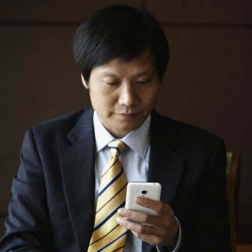 Lei Jun, CEO of China's mobile company Xiaomi, checks Xiaomi mobile phone ahead of interview during Fortune Global Forum in Chengdu