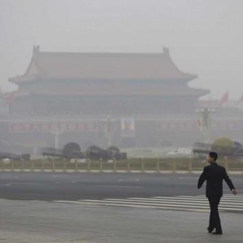 A security personnel walks near Tiananmen Gate on a heavily hazy day in Beijing