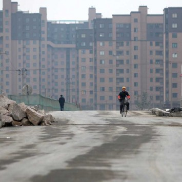 A migrant worker rides a bicycle in front of a residential site in Shanghai