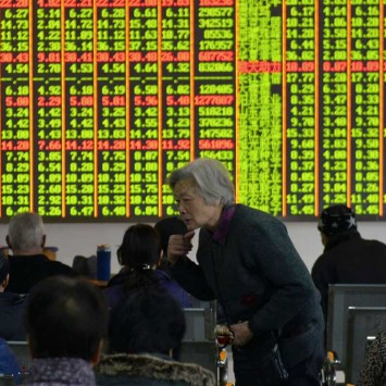 An investor speaks to others in front of an electronic board showing stock information at a brokerage house in Hangzhou