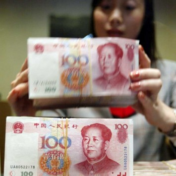 TELLER STACKS 100 YUAN NOTES AT A FOREIGN BANK IN SHANGHAI.