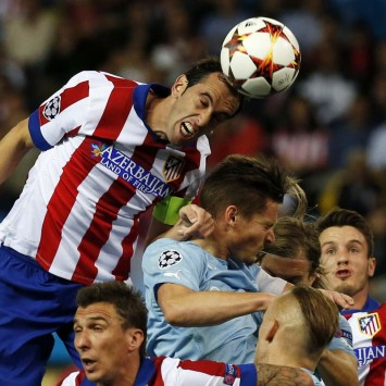Atletico Madrid's Godin heads the ball over players during their Champions League soccer match against Malmo in Madrid