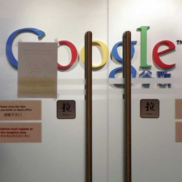 A man looks from behind a glass door at the Google Inc Shanghai office in Shanghai
