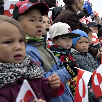 Children hold Greenland's national flags to welcome Denmark's Crown Prince Frederik, Crown Princess Mary and their children in Nuuk