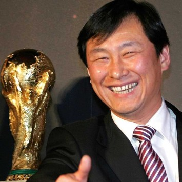 Vice president of China Football Association Nan poses next to World Cup trophy on display in Beijing