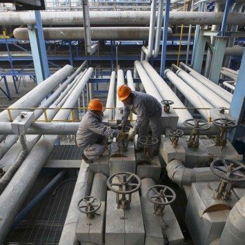 Employees close a valve of a pipe at a PetroChina refinery in Lanzhou, Gansu province