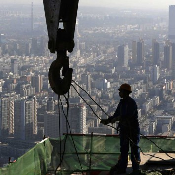 A worker operates at a construction site on the 68th storey of a building in Shenyang
