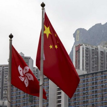 The flags of China and Hong Kong are seen in front of a large banner at Lion Rock in Hong Kong