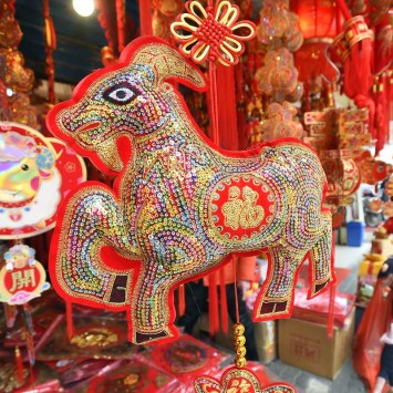 A woman gestures at a stall selling decorations ahead of the upcoming Spring Festival in Wuhan
