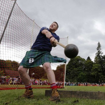 Man throws the hammer at the Birnam Highland Games in Scotland