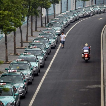 A man walks past taxis parked on the road during a strike in Hangzhou