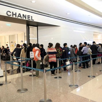 Customers line up as they wait to go inside a Chanel shop at a shopping mall in Shanghai