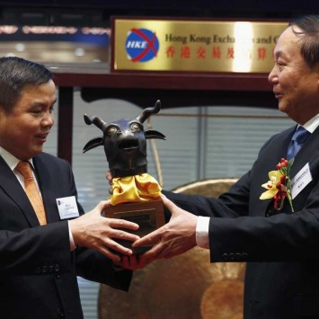 Poly Culture Group Chairman Chen offers souvenir to Hong Kong Exchanges listing committee member Liu during debut at Hong Kong Stock Exchange