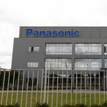 Workers walk outside the Panasonic Electric Works (Shanghai) factory building in Shanghai