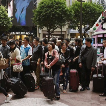 Shoppers from mainland China walk with their luggages on Russell Street at the Causeway Bay district in Hong Kong