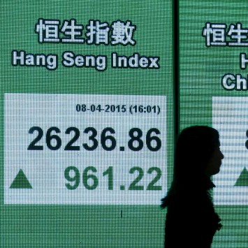 Woman walks past a panel displaying the closing Hang Seng Index outside a bank in Hong Kong